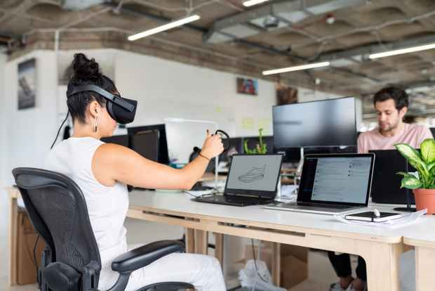 woman using laptop computer with vr headset