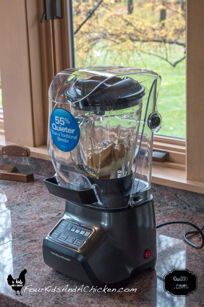 blender on the counter with the ingredients for the muffins inside it.