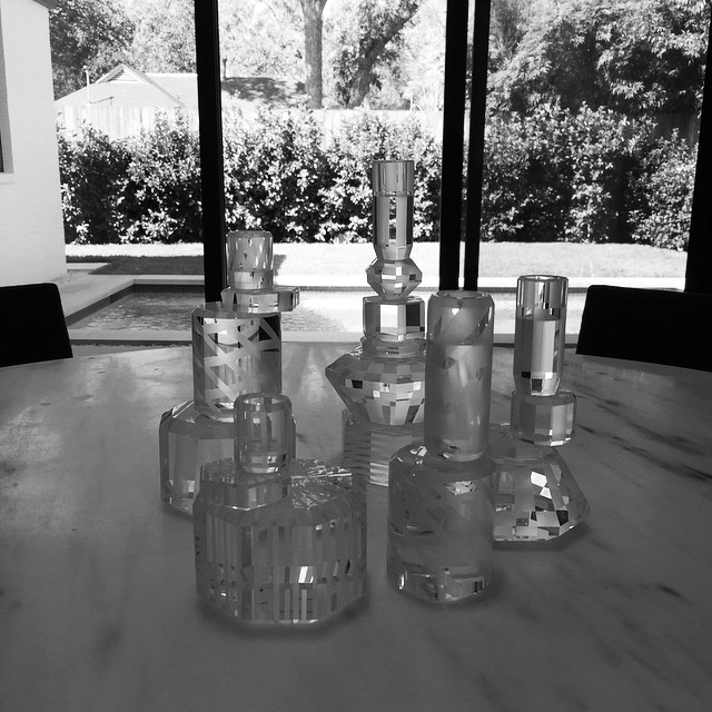 Gaia Gino candle holders on a marble dining table overlooking the pool.