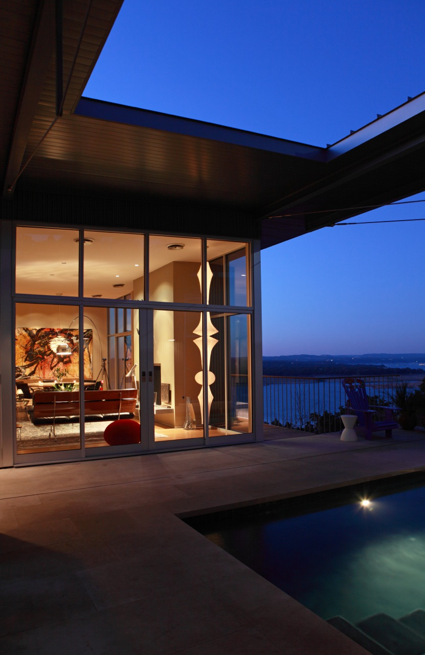 Floor to ceiling glass creates a lantern effect at night.