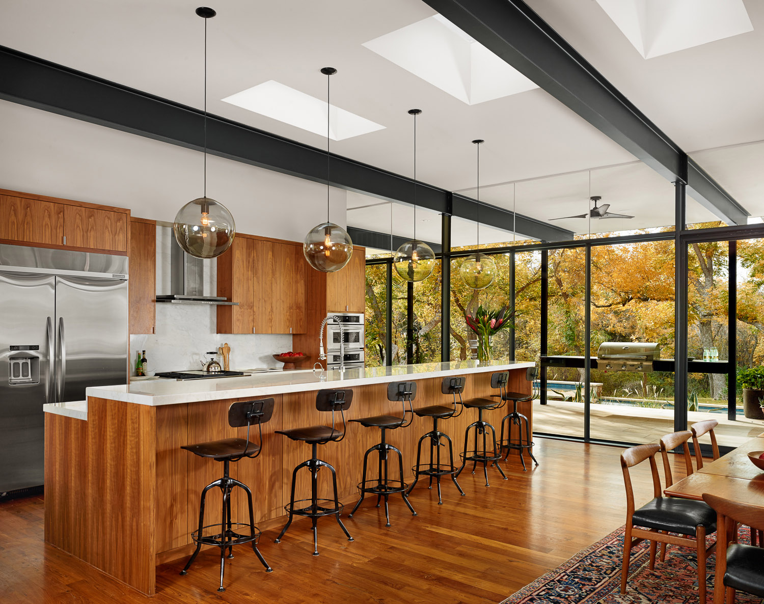 Walnut and reclaimed teak bring warmth to the structural steel.