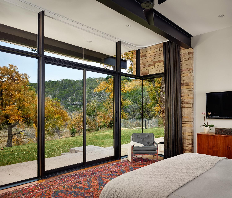 Creekside master bedroom framed in glass and steel.