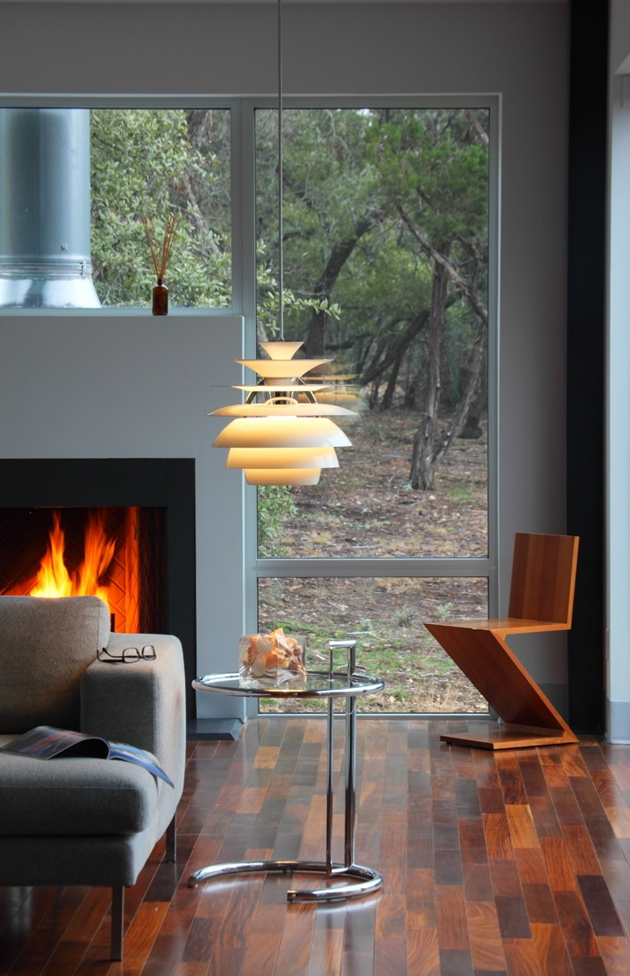 Floating fireplace surrounded by glass with views to its natural environment.