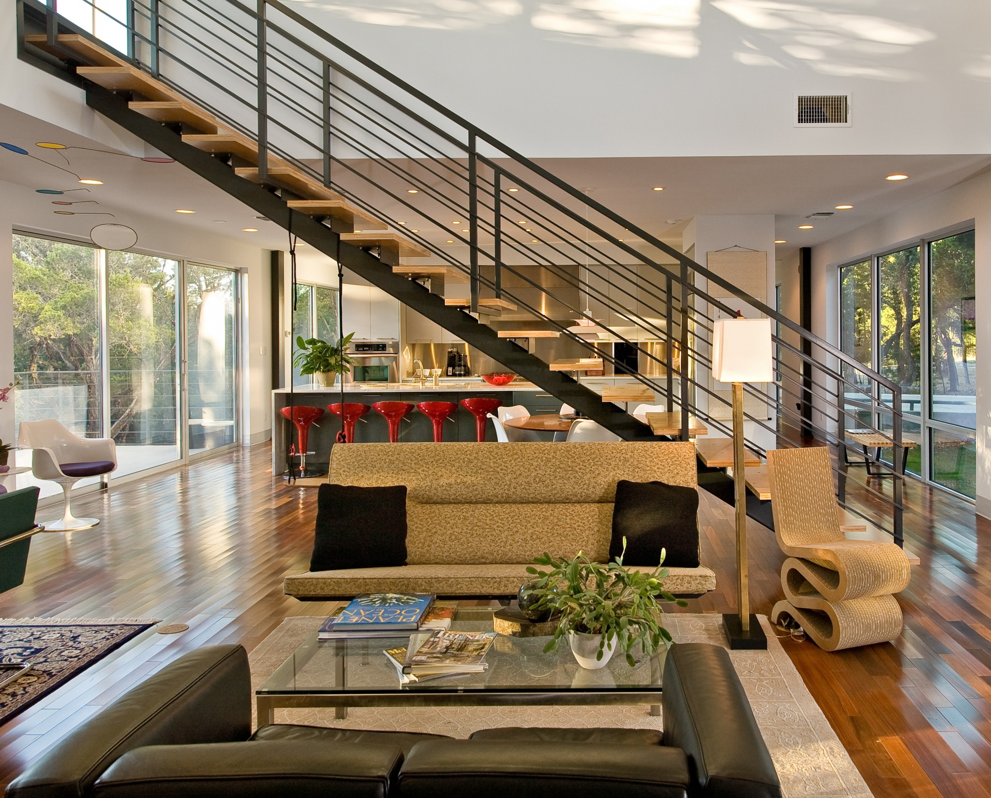 Living, dining, and kitchen are bisected with a floating steel stair system.
