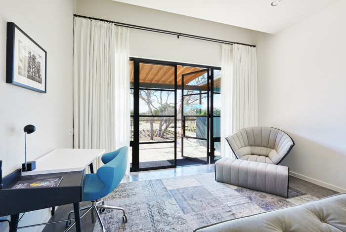 Guest room featuring steel and glass entry along with modern furnishings.