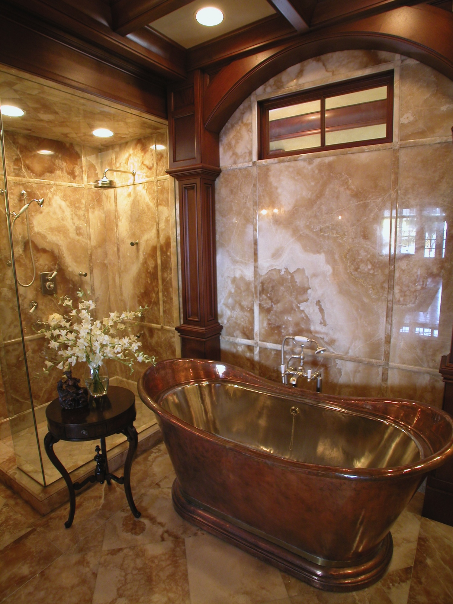Copper and nickel tub are highlighted by the Onyx paneled walls within the master bathroom.