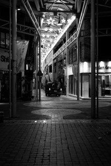 A small van parks for an evening delivery under the neon stars of a walking street.