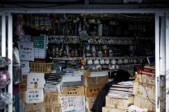A woman rummages through the goods in her shop.