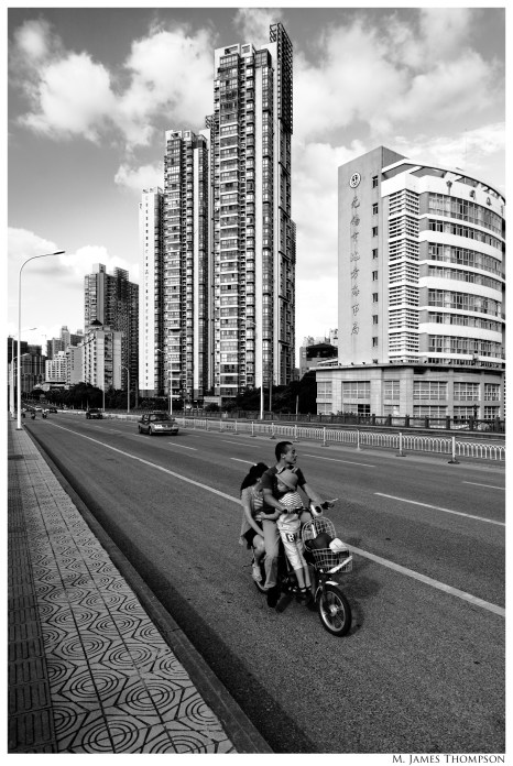 Uniform lines run from bottom right to center left and separate the two major elements of the image. The family on the scooter was very close and despite the distance the buildings appear to be very close.