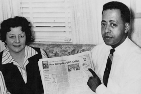 Betty and Barney Hill pose with Newspaper front page article