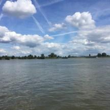 rivier met blauwe lucht en condensstrepen