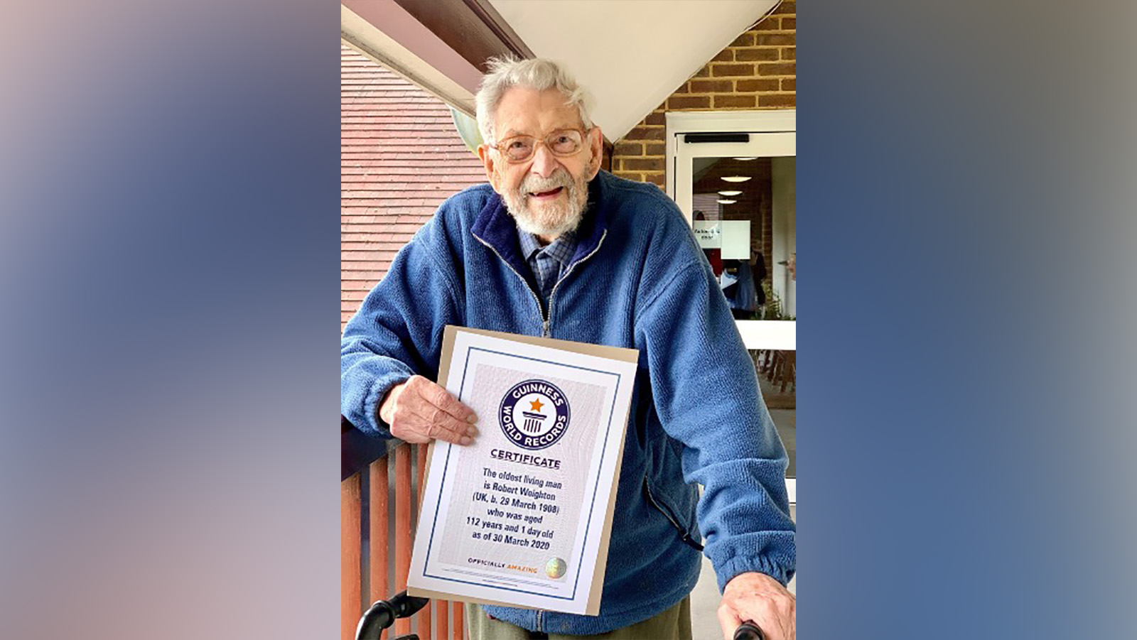 Picture of man with beard holding certificate