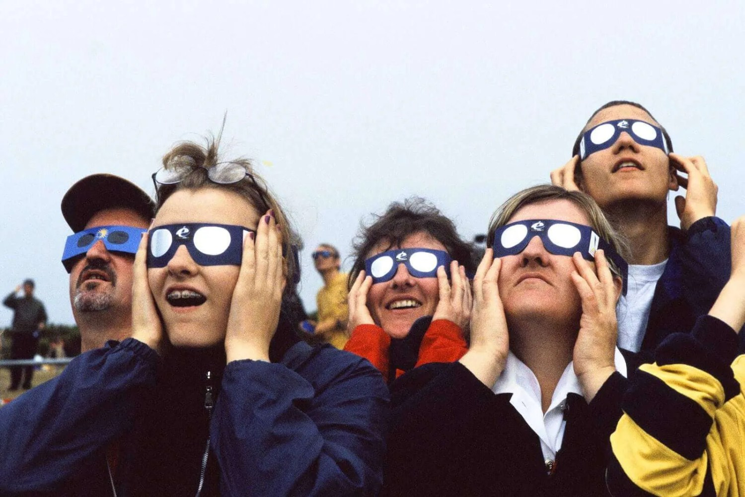 People looking up at a bright light in dark glasses