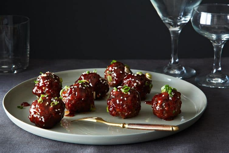Korean meatballs on gray plate with gold fork.