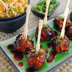 Gochujang meatballs on rectangle platter, with toothpick inserted into each meatball.