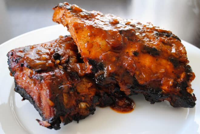 Two half racks of root beer ribs on a white plate.