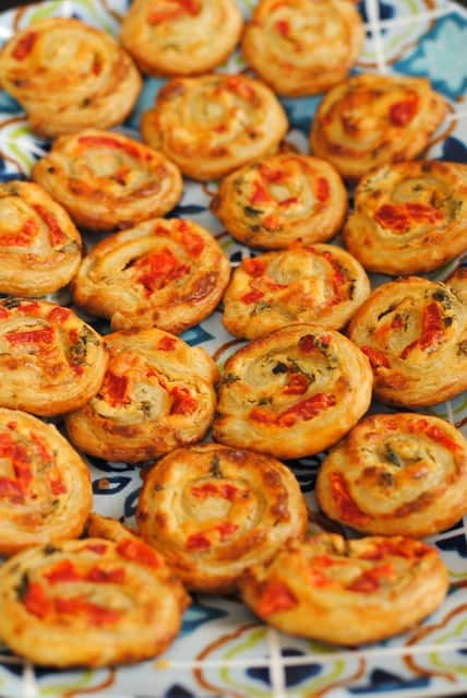 Baked puff pastry pinwheels filled with savory filling on festive platter.
