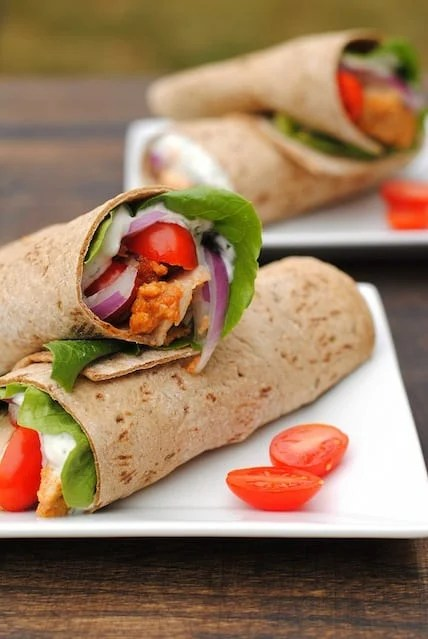 Two square plates topped with Indian chicken wrap sandwiches.