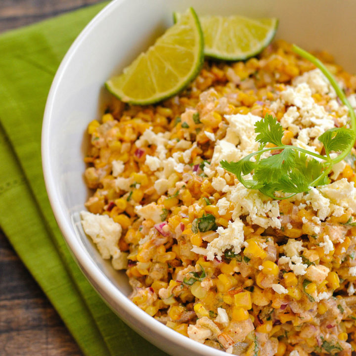 Elote salad topped with cotija cheese in white bowl, with cilantro sprig and lime wedges for garnish.