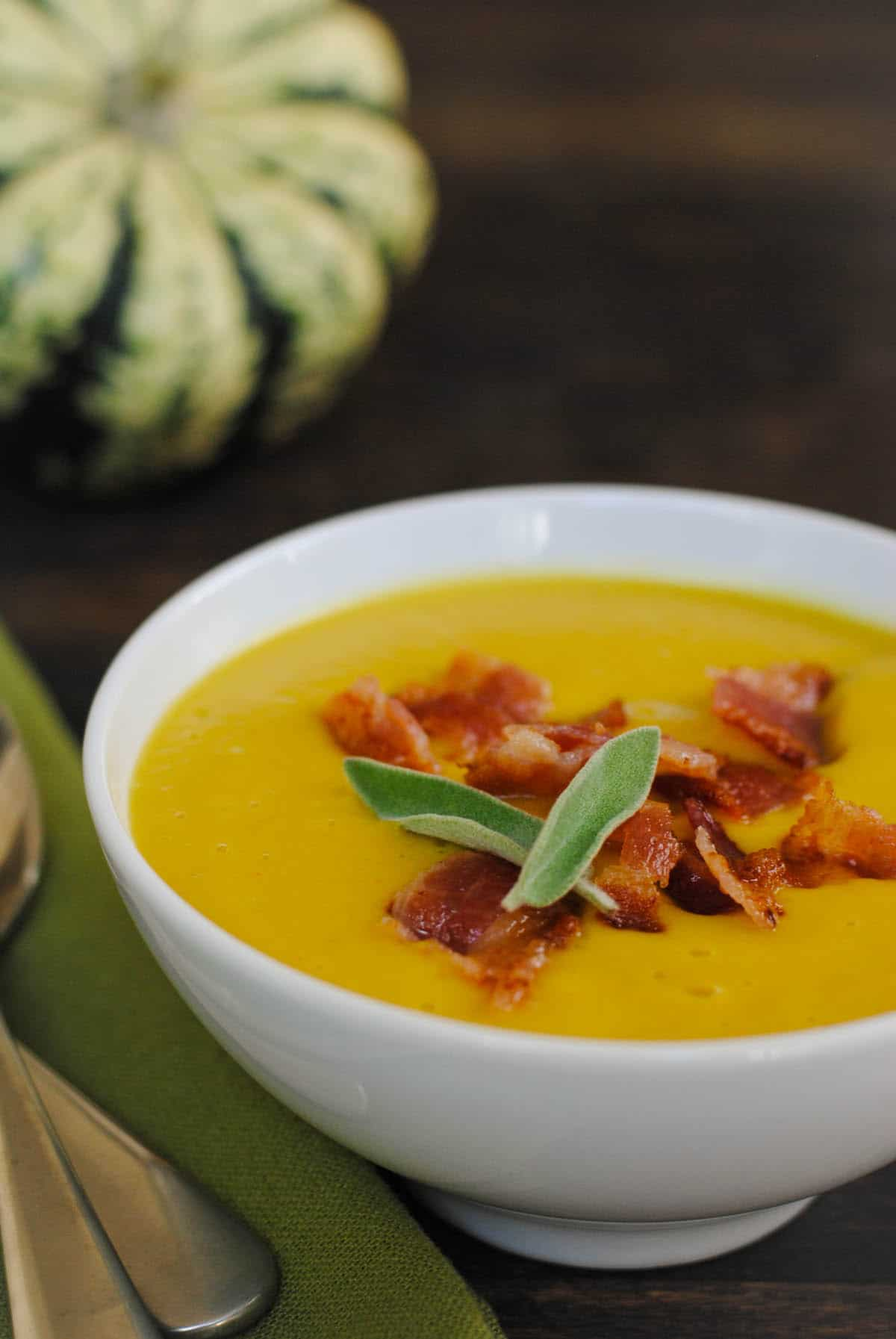 Closeup of bowl of yellow autumn soup, topped with crispy bacon and sage leaves.