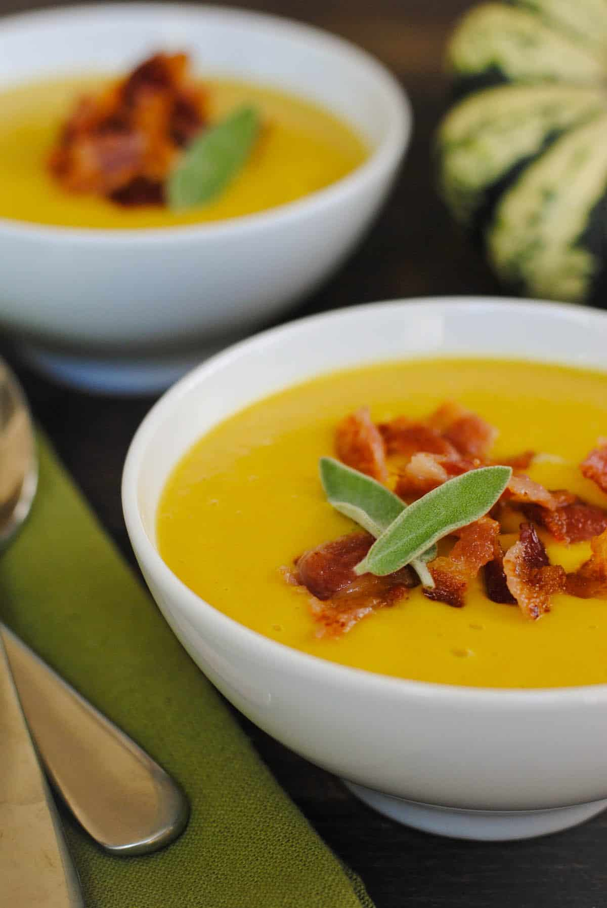 Two bowls of squash soup, topped with bacon and sage leaves.