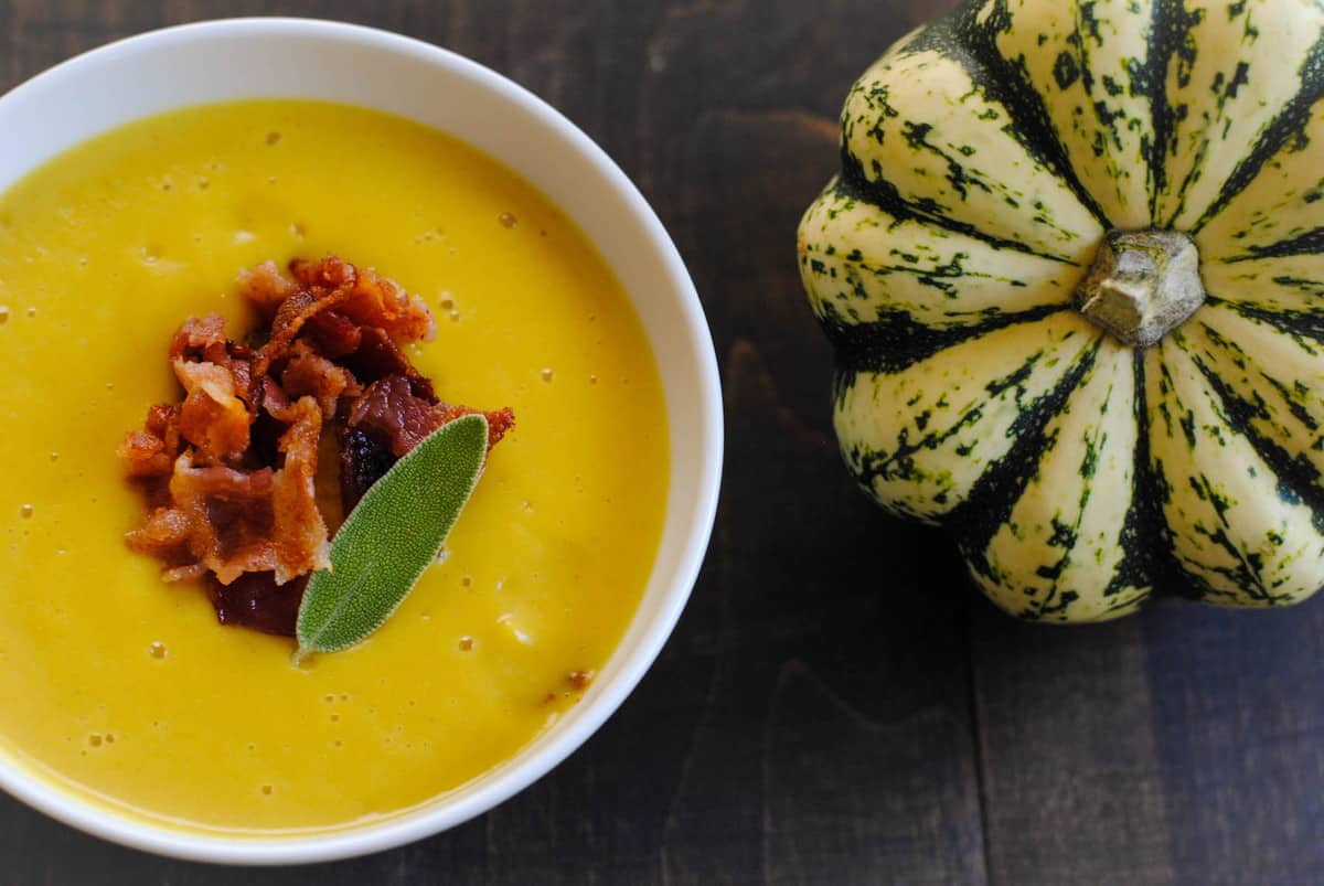 Bowl of bright yellow soup next to a sweet dumpling squash.