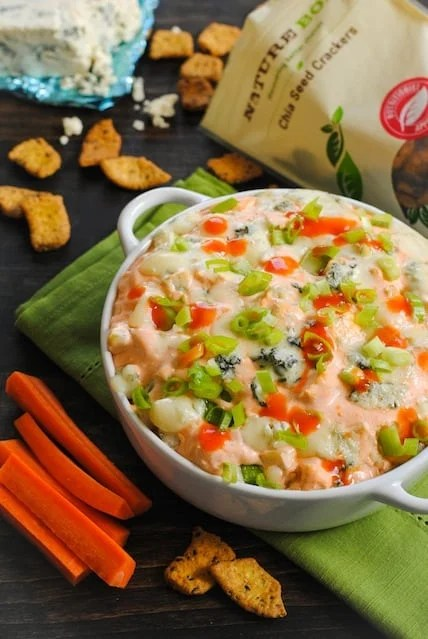 Creamy spicy dip with chicken in white round baking dish with crackers and veggies for dipping.