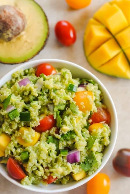 Guacamole Quinoa with Mango - all of the ingredients of guacamole, combined with quinoa and a little mango, for a tasty, healthy side dish! Serve warm or cold. | foxeslovelemons.com