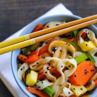 Asian stir fry with noodles in blue bowl with chopsticks.