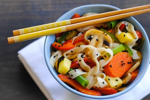 Blue bowl filled with Sweet and Sour Vegetable Stir Fry with yellow decorated chopsticks resting on top.