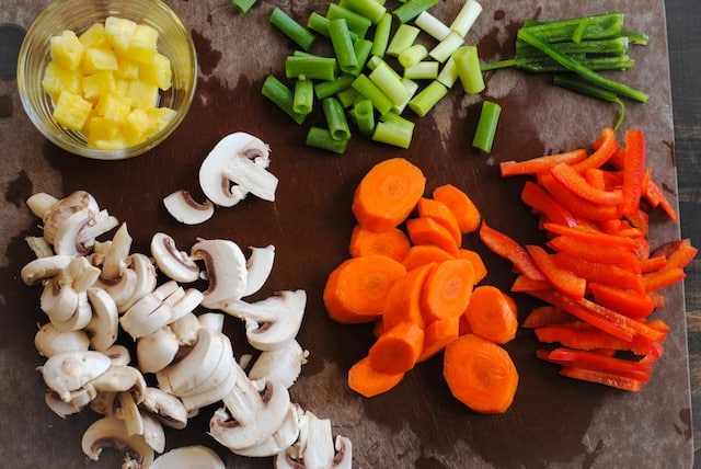 Brown cutting board with sliced mushrooms, carrots, red pepper, jalapenos, green onions and pineapple.