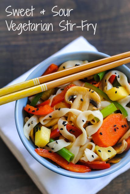 Stir fried vegetables and noodles in blue bowl with yellow accented chopsticks resting on top. Overlay: Sweet + Sour Vegetarian Stir-Fry