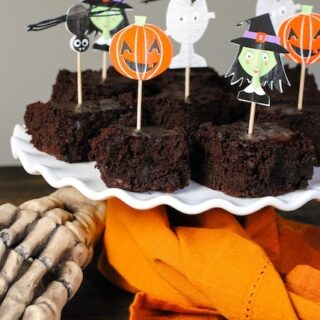 Brownies on white platter with spooky decorations.