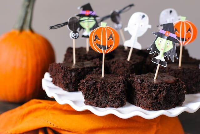 Brownies on white platter with orange napkin and pumpkin decorating scene. Pumpkin, witch, bat and ghost decorative toothpicks are stuck in brownies.