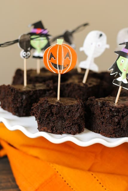 Brownies on white platter with orange napkin. Decorative spooky toothpicks are in brownies.