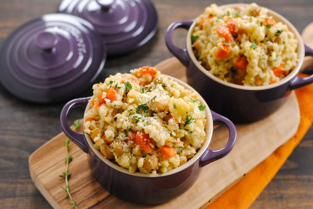Slow cooker barley risotto in small purple cocottes with lids.