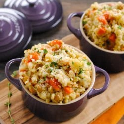 Barley and vegetable side dish in small purple pots on wooden cutting board.