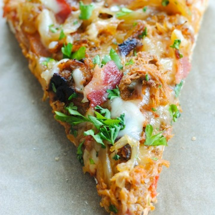 Loaded slice of pizza on tan background.