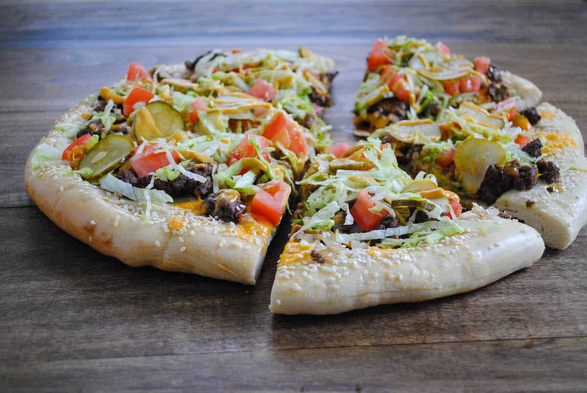 Horizontal photo of round flatbread topped with burger toppings, cut into six slices.