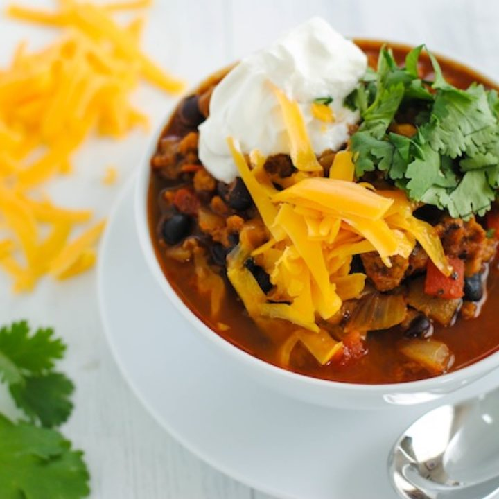 Chili topped with shredded cheddar cheese, sour cream and cilantro in white bowl, on top of white plate with spoon. Cheese and cilantro scattered on table near bowl.