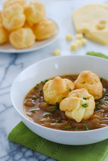 French Onion Soup with Cheese-Filled Gougeres - Classic French Onion Soup topped with little cream puffs filled with gloriously melty cheese. | foxeslovelemons.com