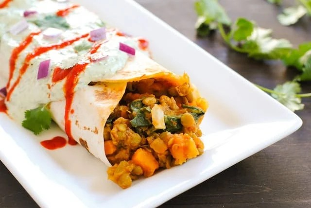 Rectangular white plate topped with burrito filled with spinach, sweet potatoes and lentils. Cilantro on table in background.