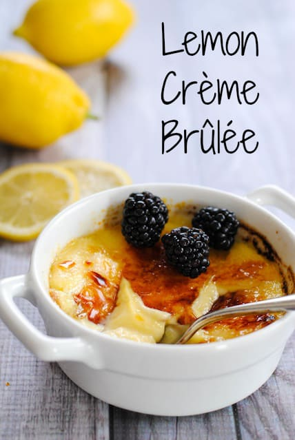 Closeup photo of lemon creme brulee topped with blackberries, with spoon breaking through torched sugar.