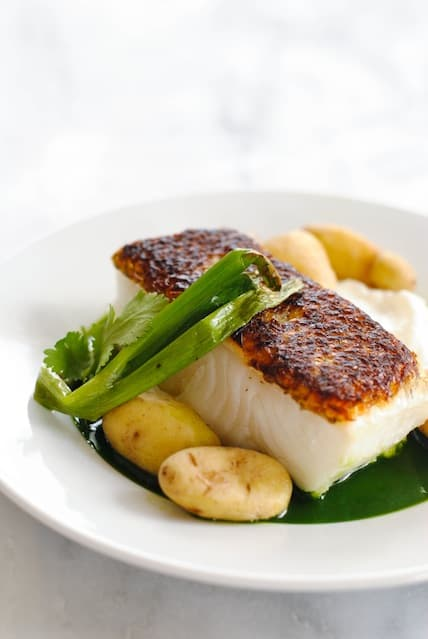 Closeup photo of seared white fish with potatoes, green onion and green sauce.