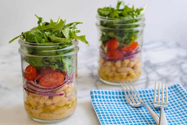 Two mason jars layered with marinated cannelini beans, sliced red onion, grape tomatoes and arugula. On light marble countertop with blue napkin and fork.