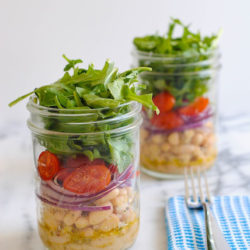 Two mason jars layered with marinated white beans, sliced red onion, grape tomatoes and arugula. On light marble countertop with blue napkin and fork.