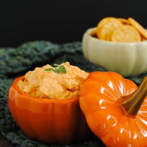 Light orange creamy dip in a ceramic pumpkin.