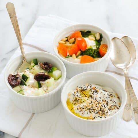 Three white ramekins of Greek yogurt topped with savory toppings.