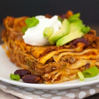 Gluten-Free Chili Lasagna - No matter your reason for skipping gluten, this casserole doesn't skip any flavor! Layers of pasta, hearty beef and bean chili, and Colby Jack cheese, topped with Greek yogurt and avocado!   foxeslovelemons.com
