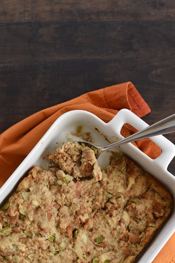 Overhead photo of white casserole dish with Thanksgiving stuffing on top of orange napkin.